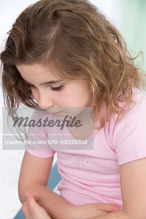 MODEL RELEASED. Young girl with tummy ache. Stock Photo - Premium Royalty-Free, Image code: 679-08228316