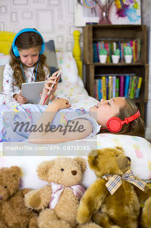 Two sisters in bedroom listening to music and watching movies. Stock Photo - Premium Royalty-Free, Image code: 679-08718165