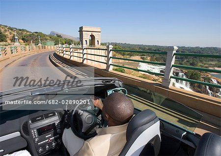 African Man Driving a Convertible Over a Dam Wall - Rear View Stock Photo - Premium Royalty-Free, Image code: 682-02890201