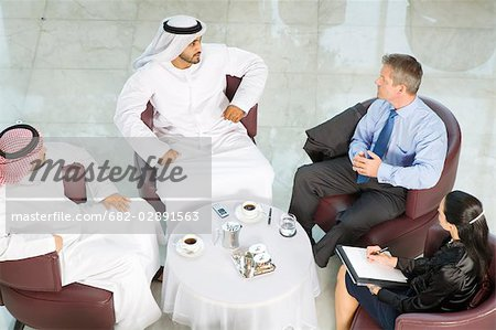 High angle view of man and woman meeting men in traditional Middle Eastern dress, Dubai, UAE