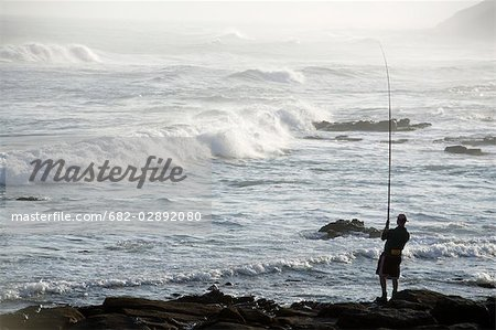 Silhouette of a Man Fishing From the Rocks Stock Photo - Premium Royalty-Free, Image code: 682-02892080