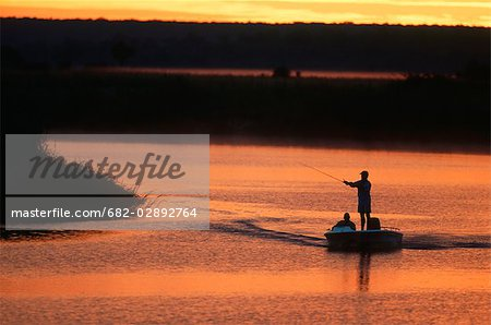 Silhouette of Fisherman in a Boat Fishing at Dawn Stock Photo - Premium Royalty-Free, Image code: 682-02892764