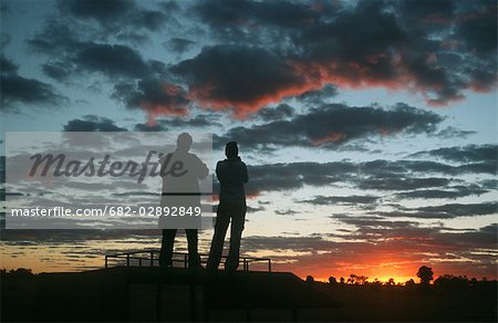 Silhouette of a Couple Admiring the Sunset Stock Photo - Premium Royalty-Free, Image code: 682-02892849