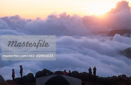 Silhouette of Campers Watching the Sunrise Over Clouds Stock Photo - Premium Royalty-Free, Image code: 682-02893023