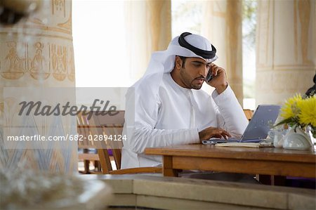 Arab Business Man using Mobile Phone and Computer, sitting on Patio Table in Restaurant Stock Photo - Premium Royalty-Free, Image code: 682-02894124