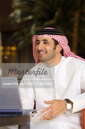 Arab Man Gesturing to Friend in Front of Laptop Computer Stock Photo - Premium Royalty-Free, Image code: 682-02894169