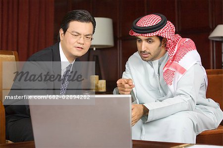 Arab Business Man and Asian Business Man Looking at Laptop Computer Screen Stock Photo - Premium Royalty-Free, Image code: 682-02894282