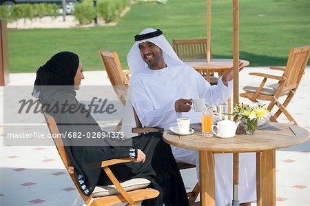 Smiling Arab husband and wife sitting on outdoor patio Stock Photo - Premium Royalty-Free, Image code: 682-02894375