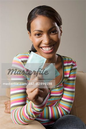 South African teen culture - Portrait of young woman holding condoms. Stock Photo - Premium Royalty-Free, Image code: 682-02896198
