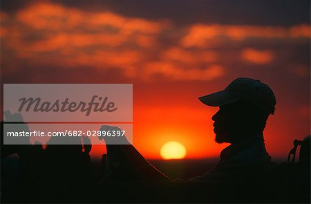 Silhouette of a Tracker at Sunset Stock Photo - Premium Royalty-Free, Image code: 682-02896397