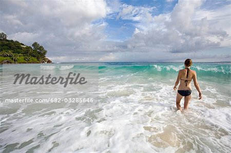 Young woman walking into ocean, Seychelles Stock Photo - Premium Royalty-Free, Image code: 682-03285646