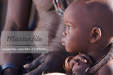 Profile view of a Himba child and torso of man, Van Zyl's Pass area, Kaokoland, Namibia Stock Photo - Premium Royalty-Free, Image code: 682-03285693