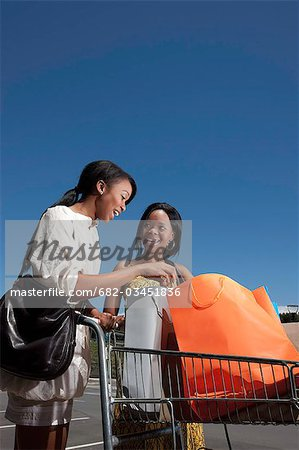Young women looking at shopping bags in trolley, KwaZulu Natal Province, South Africa Stock Photo - Premium Royalty-Free, Image code: 682-03451836