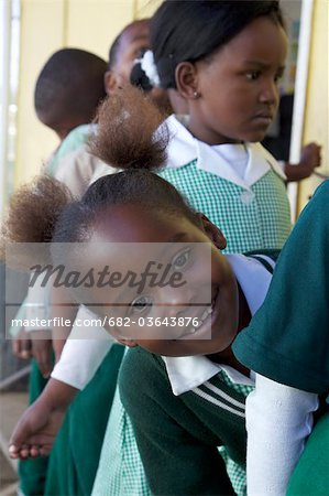 Close up shot of schoolgirl peeking out from the line, KwaZulu Natal Province, South Africa Stock Photo - Premium Royalty-Free, Image code: 682-03643876