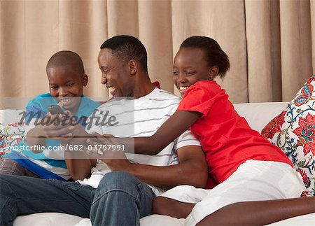Man and children fighting over remote control, Johannesburg, South Africa Stock Photo - Premium Royalty-Free, Image code: 682-03797991