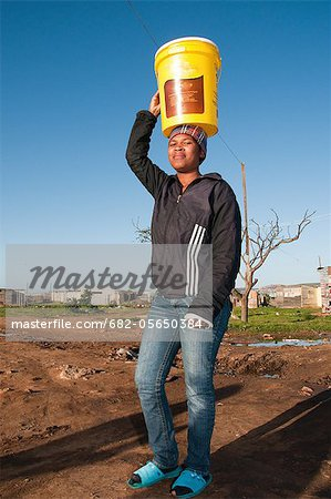 Young woman carrying water to house, Missionvale, Port Elizabeth, Eastern Cape Province, South Africa Stock Photo - Premium Royalty-Free, Image code: 682-05650384