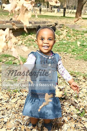 Toddler girl throwing autumn leaves up in air and smiling broadly, Johannesburg, South Africa Stock Photo - Premium Royalty-Free, Image code: 682-05650593