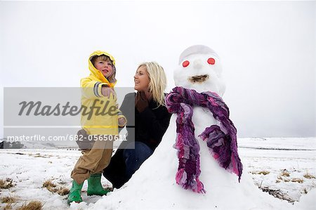 A young woman and a young boy near a snowman, Kamberg, KwaZulu-Natal Province, South Africa Stock Photo - Premium Royalty-Free, Image code: 682-05650611