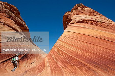 A woman in the wave, Vermilion North Coyote Buttes, Paria Canyon-Vermilion Cliffs wilderness, Vermilion National Monument, Arizona, USA. Stock Photo - Premium Royalty-Free, Image code: 682-05977425