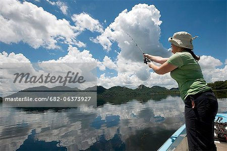 Woman fishing from boat, Mazvikadei dam, Mashonlaland West Province, Zimbabwe Stock Photo - Premium Royalty-Free, Image code: 682-06373927
