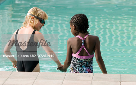 Two multi-racial girls going into a pool. Windhoek, Namibia. Stock Photo - Premium Royalty-Free, Image code: 682-07281440