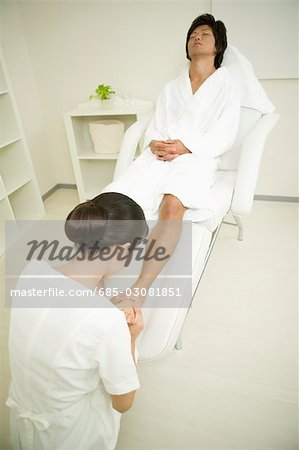 Young man receiving foot massage Stock Photo - Premium Royalty-Free, Image code: 685-03081851