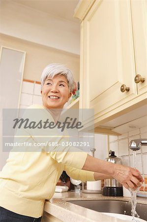 Senior woman standing in kitchen Stock Photo - Premium Royalty-Free, Image code: 685-03082291