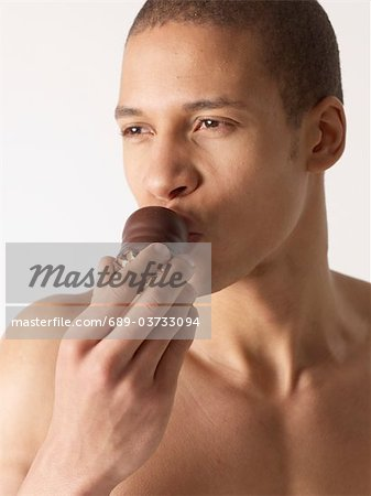 Barechested man eating chocolate marshmallow Stock Photo - Premium Royalty-Free, Image code: 689-03733094