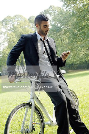 Businessman with bicycle and cell phone in park Stock Photo - Premium Royalty-Free, Image code: 689-03733401