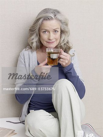 Senior woman with a glass of tea Stock Photo - Premium Royalty-Free, Image code: 689-03733675