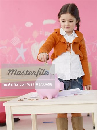 Girl inserting money into piggy bank Stock Photo - Premium Royalty-Free, Image code: 689-03733698