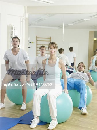 Three men and a woman exercising with fitness balls Stock Photo - Premium Royalty-Free, Image code: 689-03733760