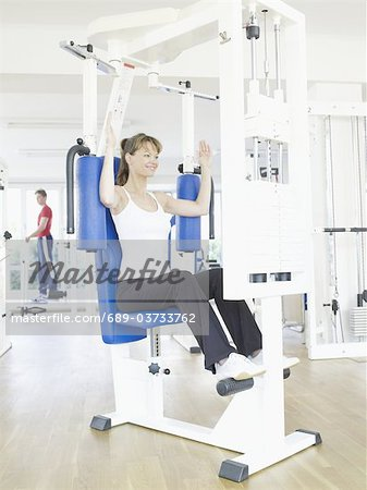 Woman exercising at a health club Stock Photo - Premium Royalty-Free, Image code: 689-03733762