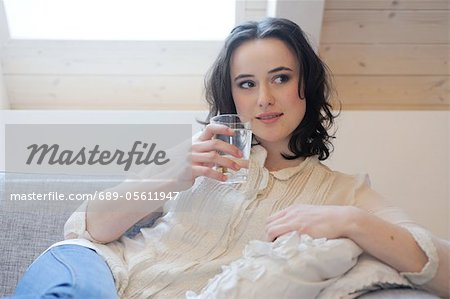 Young woman on couch drinking glass of water Stock Photo - Premium Royalty-Free, Image code: 689-05611947