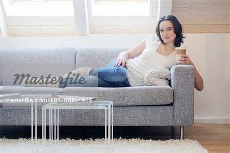 Young woman on couch drinking Latte Macchiato Stock Photo - Premium Royalty-Free, Image code: 689-05611949