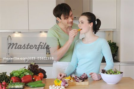 Young couple in kitchen preparing salad Stock Photo - Premium Royalty-Free, Image code: 689-05611998