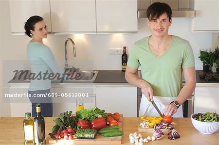 Young couple in kitchen preparing salad Stock Photo - Premium Royalty-Free, Image code: 689-05612001
