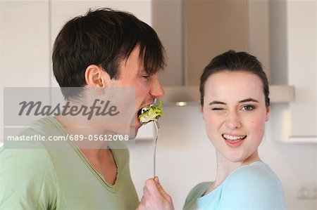Young woman feeding man with salad Stock Photo - Premium Royalty-Free, Image code: 689-05612008