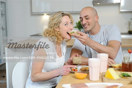 Happy couple having breakfast in kitchen Stock Photo - Premium Royalty-Free, Image code: 689-05612036