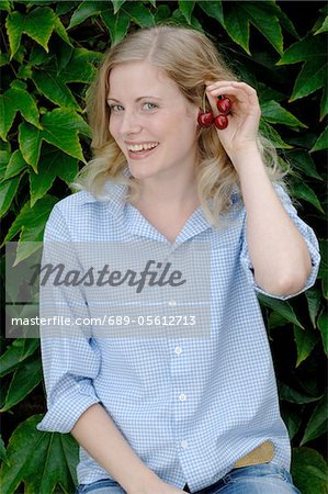 Happy young woman with cherries Stock Photo - Premium Royalty-Free, Image code: 689-05612713