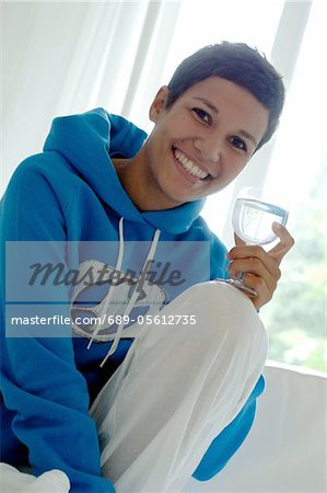 Young woman holding glass of water on couch Stock Photo - Premium Royalty-Free, Image code: 689-05612735