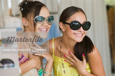 Girls Trying on Sunglasses in store Stock Photo - Premium Royalty-Free, Image code: 693-03299494