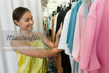 Young Woman Looking Through Clothing Rack in store Stock Photo - Premium Royalty-Free, Image code: 693-03299495