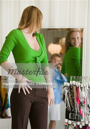Woman Looking at Clothing in Store Mirror Stock Photo - Premium Royalty-Free, Image code: 693-03299496