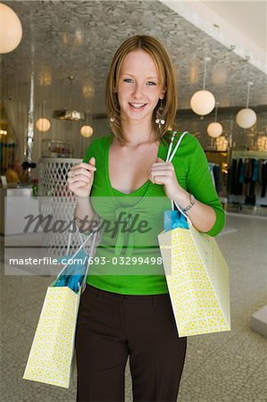 Girl Holding Shopping Bags in Boutique, portrait Stock Photo - Premium Royalty-Free, Image code: 693-03299498