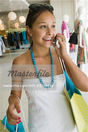 Girl Holding Using Cell Phone in clothing store Stock Photo - Premium Royalty-Free, Image code: 693-03299499