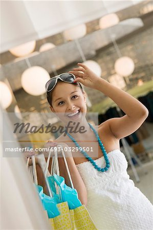Woman Trying on Sunglasses in Clothing Store, front view Stock Photo - Premium Royalty-Free, Image code: 693-03299501