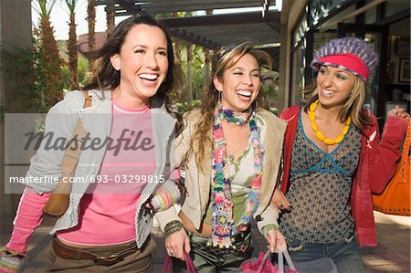 Three stylish friends walking near shopping centre Stock Photo - Premium Royalty-Free, Image code: 693-03299815