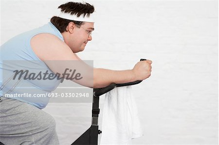 Overweight man on Exercise Bike, side view Stock Photo - Premium Royalty-Free, Image code: 693-03302948