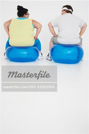 Overweight man and woman Resting on Exercise Balls, back view Stock Photo - Premium Royalty-Free, Image code: 693-03302950